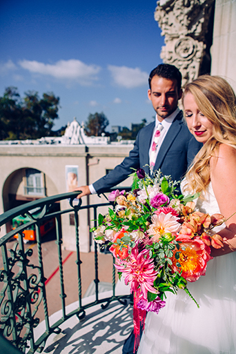 Eclectic bohemian wedding at Museum of Man in San Diego bride strapless tulle ball gown with a sweetheart neckline and lace bodice with groom slate blue suit with white dress shirt and white and pink floral long tie on balcony with bright floral arrangements