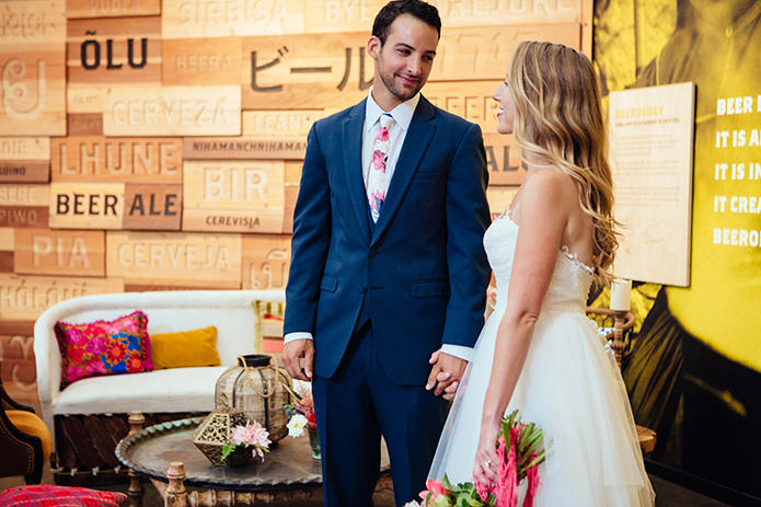 Eclectic bohemian wedding at Museum of Man in San Diego bride strapless tulle ball gown with a sweetheart neckline and lace bodice with groom slate blue suit with white dress shirt and white and pink floral long tie holding hands with yellow and word background