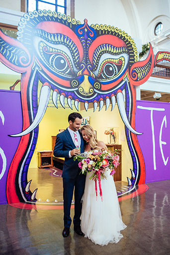 Eclectic bohemian wedding at Museum of Man in San Diego bride strapless tulle ball gown with a sweetheart neckline and lace bodice with groom slate blue suit with white dress shirt and white and pink floral long tie with colorful dragon entrance