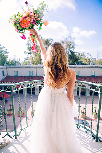 Eclectic bohemian wedding at the museum of man in san diego bride strapless tulle ball gown with a sweetheart neckline and lace bodice with bright pink and purple floral bridal bouquet in the air wedding photo idea for bride