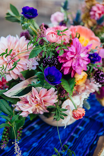 Eclectic bohemian wedding at the museum of man in san diego bright pink and blue flower centerpiece arrangement on blue patterned table linen with gold vase decor wedding photo idea