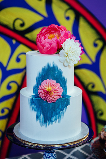 Eclectic bohemian wedding at the museum of man in san diego brown wood dessert table with two tier white wedding cake with blue design decor with smaller table and assortment of desserts with purple painted design background wedding photo idea close up of the cake