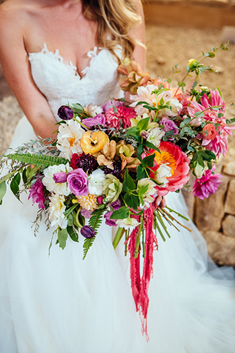 Eclectic bohemian wedding at the museum of man in san diego bright pink and purple floral bouquet with hanging ribbon decor close up wedding photo idea for bride