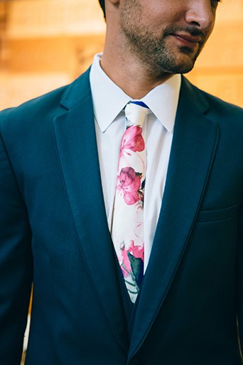 Eclectic bohemian wedding at the museum of man in san diego groom slate blue suit with white dress shirt and long white and pink floral tie close up wedding photo idea for groom