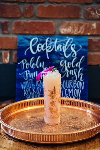 Eclectic bohemian wedding at the museum of man in san diego gold tray with crystal drink glass and blue painting with white calligraphy writing with brick wall background wedding photo idea