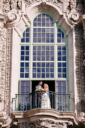 Eclectic bohemian wedding at Museum of Man in San Diego bride strapless tulle ball gown with a sweetheart neckline and lace bodice with groom slate blue suit with white dress shirt and white and pink floral long tie on the balcony