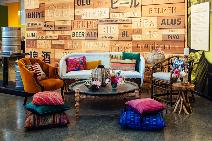 Eclectic bohemian wedding at the museum of man san diego brown wood table with rustic decor and patterned pillows on the floor wedding photo idea and the worded background with lounge decor