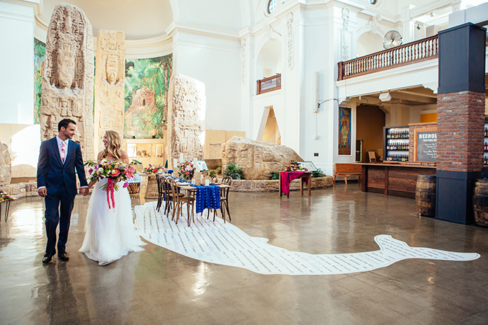 Eclectic bohemian wedding at Museum of Man in San Diego bride strapless tulle ball gown with a sweetheart neckline and lace bodice with groom slate blue suit with white dress shirt and white and pink floral long tie standing in room with table decor and white whale rug