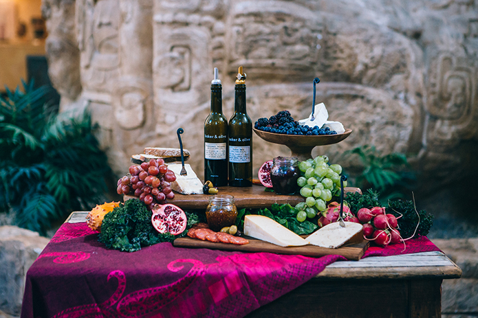 Eclectic bohemian wedding at the museum of man in san diego wine and cheese table with assortment of cheeses and fruit on platter with wine for appetizers and cocktail hour wedding photo idea