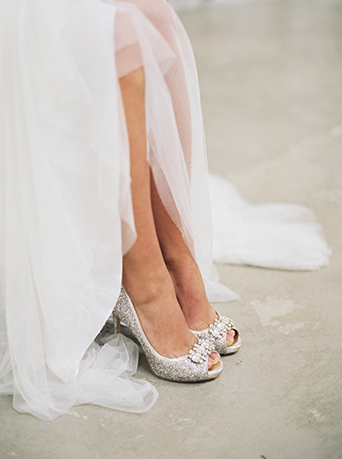 Downtown LA wedding at the honeypot rose gold inspired shoot bride long a line tulle gown with a plunging neckline and dress pulled up to see shoes silver sequined heels with peep toe and crystal jewel piece on top wedding photo ideas for bride