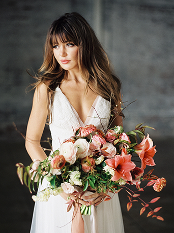 Downtown LA wedding at the honeypot rose gold inspired shoot bride long tulle a line gown with lace detail on top and a plunging neckline holding white and pink floral bridal bouquet with rose gold ribbon decor and greenery accents with hair down in loose waves
