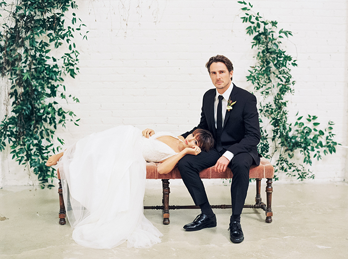 Downtown LA wedding at the honeypot rose gold inspired shoot bride long a line tulle gown with lace detail on top and a plunging neckline with groom black suit with long black tie and white dress shirt with white and green floral boutonniere