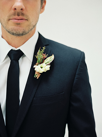 Dowtown LA wedding at the honeypot rose gold inspired shoot groom black suit with long black tie and white boutonniere with green accents wedding photo ideas for the groom before the ceremony