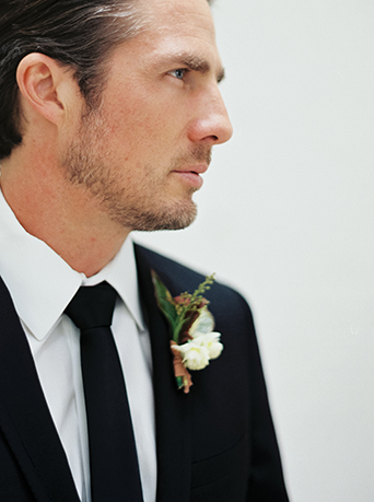 Downtown LA wedding at the honeypot rose gold inspired shoot groom black suit with long black tie and white dress shirt with white boutonniere and green accents wedding photo ideas for groom before ceremony