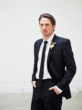 Downtown LA wedding at the honeypot rose gold inspired shoot groom black suit with long black tie and white dress shirt and white boutonniere with green accents hands in pockets wedding photo ideas for groom before ceremony