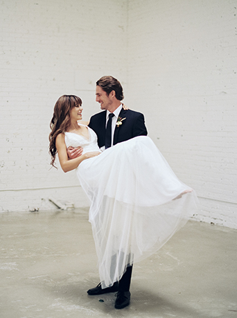 Downtown LA wedding at the honeypot rose gold inspired shoot groom black suit with white dress shirt and long black tie and white and green floral boutonniere holding bride long a line tulle gown with lace detail on top and a plunging neckline wedding photo ideas