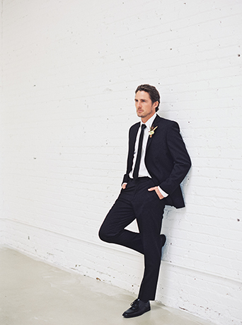 Downtown LA wedding at the honeypot rose gold inspired shoot groom black suit with long black tie and white dress shirt with white boutonniere and green accents leaning against wall wedding photo ideas for groom before ceremony