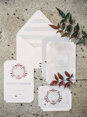 Downtown LA wedding at the honeypot rose gold inspired shoot white invitations and white envelopes with red patterned and silver writing on invitations with green floral decor sitting on grey stone background with black decor wedding photo ideas