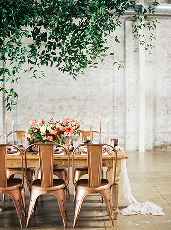 Downtown LA wedding at the honeypot rose gold inspired shoot reception table set up brown wood table with rose gold metallic chairs with white and pink flower centerpieces with greenery hanging decor over table wedding photo ideas