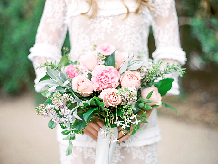 Greenhouse styled summer garden wedding shoot in San Juan Capistrano bride wearing lace gown with sleeves and small ruffle accents with emerald green wedding ring holding white and pink rose and peony floral bridal bouquet blush and pink with green floral accents