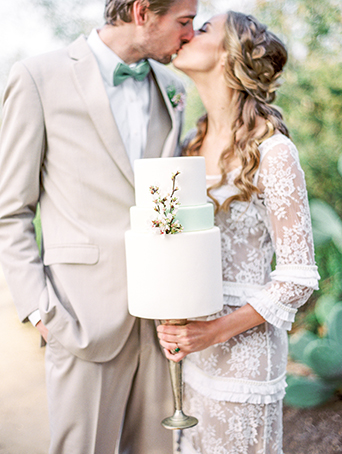 Greenhouse styled summer garden wedding shoot in san juan capistrano bride lace gown with sleeves and small ruffle accents and groom tan suit with white dress shirt and matching vest with black dress shoes and mint green bow tie with white and green floral boutonniere holding cake
