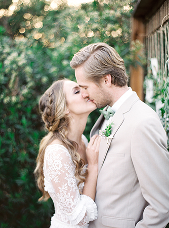 Greenhouse styled summer garden wedding shoot bride lace gown with sleeves and small ruffle accents and groom with tan suit and white dress shirt with matching vest and black dress shoes with mint green bow tie and white and green floral boutonniere