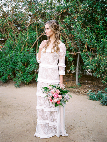 Greenhouse styled summer garden wedding shoot in San Juan Capistrano bride full lace gown with sleeves and small ruffle accents with emerald green wedding ring holding bridal bouquet blush pink and white rose and peony flowers with green floral accents