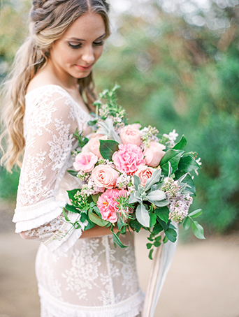 Greenhouse styled summer garden wedding shoot in San Juan Capsitrano bride lace gown with sleeves and small ruffle accents holding floral bridal bouquet with blush pink and white rose and peony flowers with green floral accents