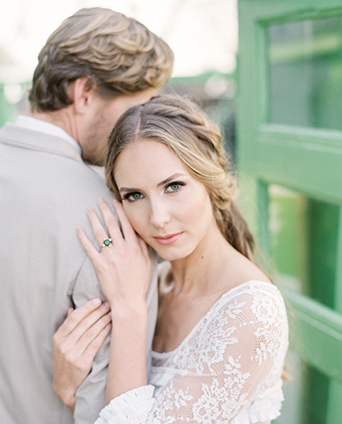 Greenhouse styled wedding shoot bride lace gown with sleeves and small ruffle accents and emerald green wedding ring with groom tan suit with white dress shirt and matching vest with black dress shoes and mint green bow tie with white and green floral boutonniere