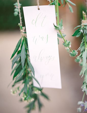 Greenhouse styled summer garden wedding shoot in San Juan Capistrano close up hanging white note with green calligraphy writing hanging from brown rustic decor string in green flower and lavender florals wedding photo idea in greenery