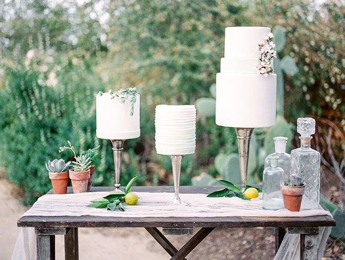 Greenhouse styled summer garden wedding shoot in San Juan Capistrano brown wood rustic dessert table close up with white wedding cakes and floral accents and rustic decor wedding photo idea