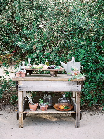 Greenhouse styled summer garden wedding shoot in San Juan Capistrano full dessert table grape and cheese platter on brown wood tray with olive oil and succulent floral decor wedding photo idea with rustic elements