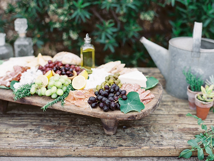 Greenhouse styled summer garden wedding shoot in San Juan Capistrano grape and cheese platter on brown wood tray with olive oil and succulent floral decor wedding photo idea with rustic elements