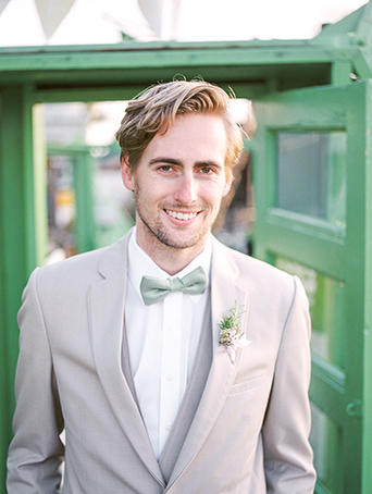 Greenhouse styled summer garden wedding shoot in San Juan Capistrano groom wearing tan suit with white dress shirt with matching vest and brown dress shoes and mint green bow tie with white and green floral boutonniere