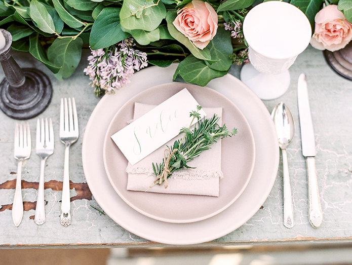 Greenhouse styled summer garden wedding shoot in San juan Capsitrano place setting with green floral accents brown wood table with silver grey chairs and white place settings with green floral garland centerpieces rustic decor for wedding reception dining ideas
