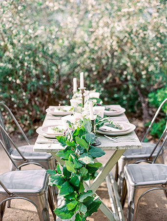 Greenhouse styled summer garden wedding shoot in San Juan Capistrano full table set up brown wood table with silver grey chairs and white place settings with green floral garland centerpieces rustic decor for wedding reception dining ideas