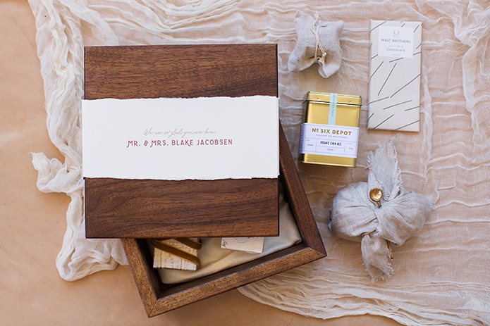 San Miguel beach wedding shoot wood box with bride and groom names on white paper with light pink writing and white decor and gold box with jewelry with sheer white linen background wedding photo idea