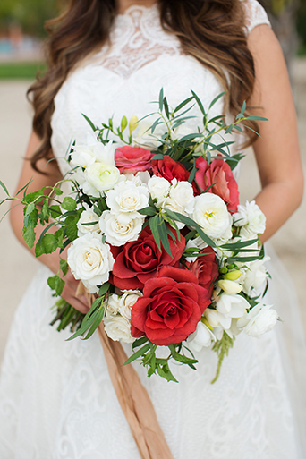 San Miguel beach wedding photo shoot bride lace ball gown with illusion neckline and wavy hair down to one side holding red and white bridal bouquet with groom tan suit with white dress shirt and coral pink bow tie and floral boutonniere