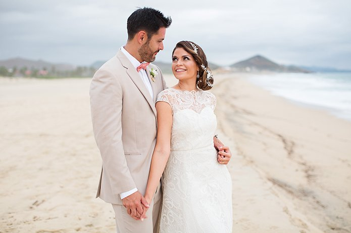 San Miguel beach wedding photo shoot bride lace ball gown with illusion neckline with hair updo and side bun and flower decor and groom tan suit with white dress shirt and coral pink bow tie with floral boutonniere close up on the beach