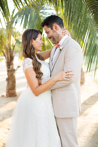 San Miguel beach wedding shoot bride lace ball gown with illusion neckline and wavy hair down to one side and groom tan suit with white dress shirt and coral pink bow tie with floral boutonniere hugging bride close up