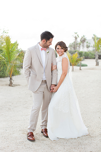 San Miguel beach wedding photo shoot bride lace ball gown with illusion neckline and hair updo in side bun with floral decor and groom tan suit with white dress shirt and coral pink bow tie with floral boutonniere holding hands