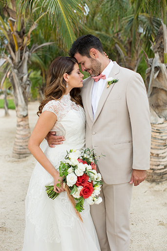 San Miguel beach wedding photo shoot bride lace ball gown with illusion neckline wavy hair down to one side and groom tan suit with white dress shirt and coral pink tie with floral boutonniere hugging