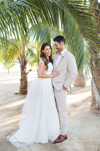 San Miguel beach wedding shoot bride lace ball gown with illusion neckline and wavy hair down to one side and groom tan suit with white dress shirt and coral pink bow tie with floral boutonniere laughing