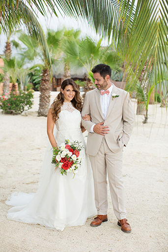 San Miguel beach wedding photo shoot bride lace ball gown with illusion neckline and wavy hair down to one side and groom tan suit with white dress shirt and coral pink bow tie and floral boutonniere on the beach