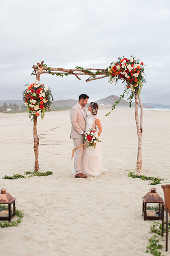 San Miguel beach wedding photo shoot bride lace ball gown with illusion neckline and hair updo in side bun with flower decor and groom tan suit with white dress shirt and coral pink bow tie with floral boutonniere under arch with red and white floral decor holding white and red floral bridal bouquet
