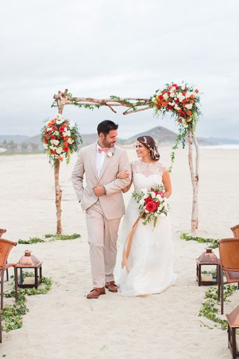 San Miguel beach wedding photo shoot bride lace ball gown with illusion neckline and hair updo side bun with flower decor and groom tan suit with white dress shirt and coral bow tie with floral boutonniere walking away from arch with red and white floral decor holding white and red floral bridal bouquet