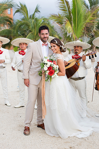 San Miguel beach wedding photo shoot bride lace ball gown with illusion neckline and hair updo in side bun with flower decor and groom tan suit with white dress shirt and coral pink bow tie and floral boutonniere with mariachi band in all white wearing sombreros