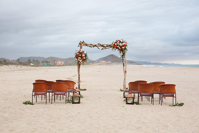 San Miguel beach wedding photo shoot ceremony arch with white and red flowers on the sand with dark brown chairs on both sides wedding photo idea for ceremony arch decoration