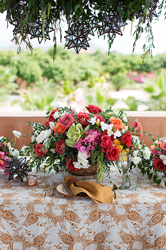 San Miguel beach wedding photo shoot flower centerpiece decor with pink red orange florals and green accents on table with brown and white patterned tablecloth reception table wedding photo idea