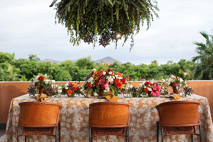 San Miguel beach wedding photo shoot full table set up with brown and white patterned table cloth with red orange and white floral centerpiece and hanging greenery with brown chairs reception table area for guests